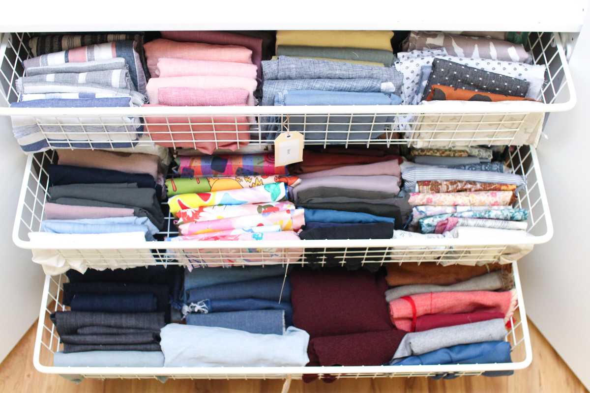 Megan Nielsen's fabric stash | All fabric folded KonMari style and sorted by fabric type. Tubs are used for scraps which are sorted by type.