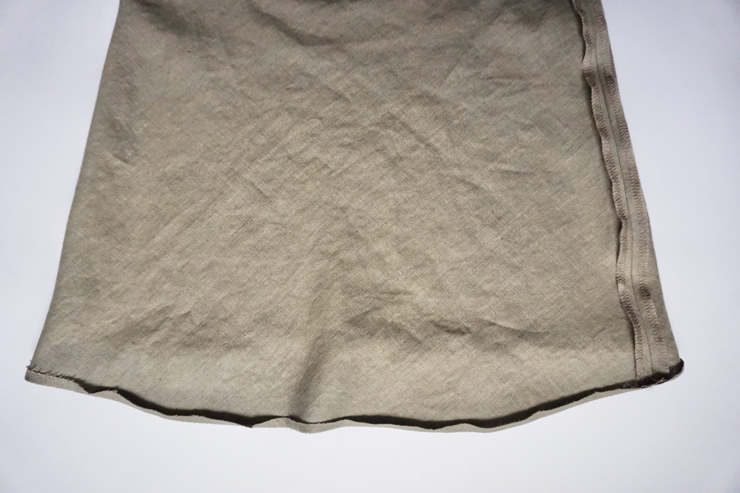 Fold the hem inwards towards the wrong side of the fabric along the line of stitching.